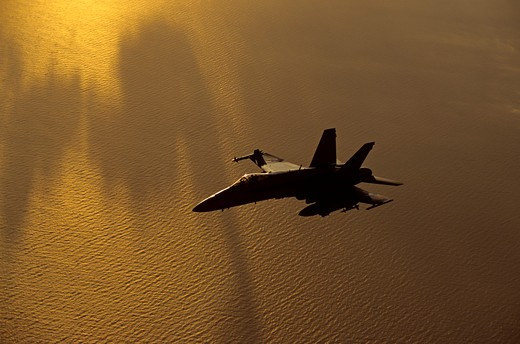Moody golden sunset shot of a US Navy F/A-18C Hornet over the Pacific Ocean : Stock Photo