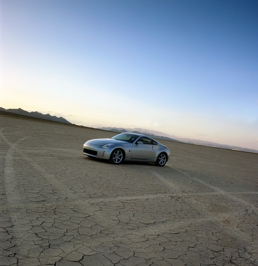 2004 Nissan 350Z in the desert dry lake bed salt flats with dramatic sky and clouds : Stock Photo