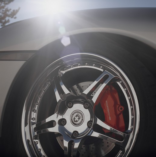 2004 Porsche 996 Turbo parked in an industrial area close up shots shot of the wheel and tire with the sun peaking over the hood sun spots flair : Stock Photo