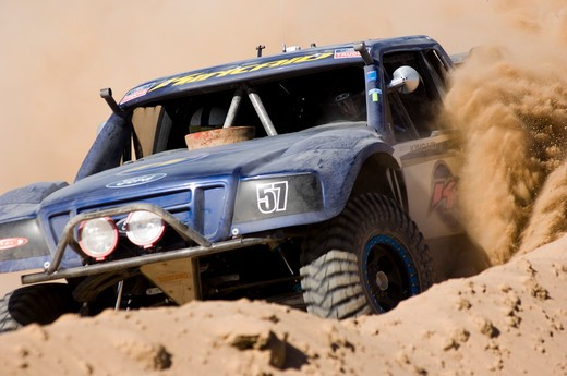 Baja desert race trucks spinning and kicking up dirt and dust. : Stock Photo