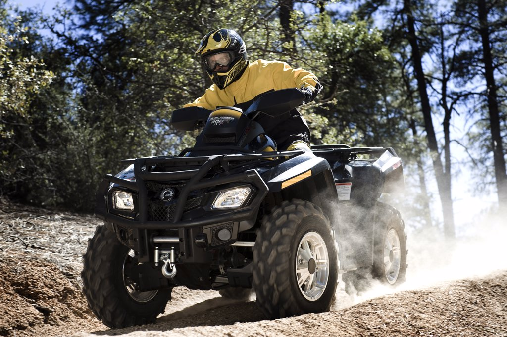 Stock Photo: 4093-3839 Can-Am ATV riding through forest terrain
