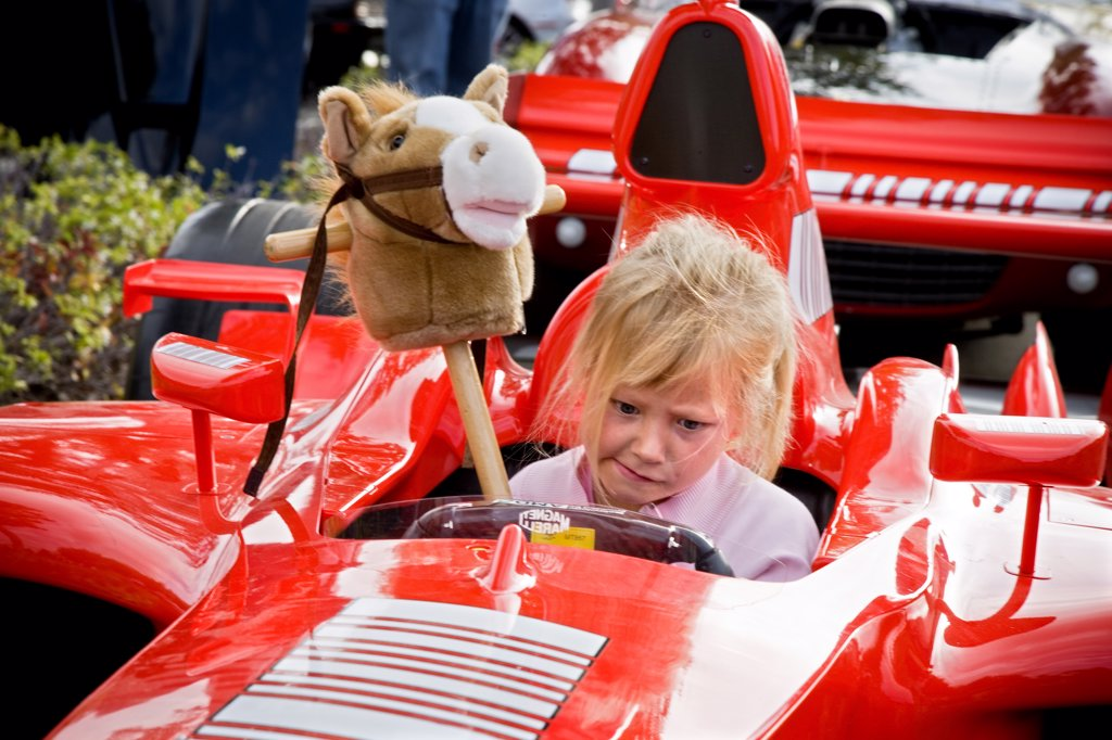 Stock Photo: 4093-5501 view of a Ferrari roadster racer at a car show in the morning and a young grill child sitting inside with a funny look and a horse toy.