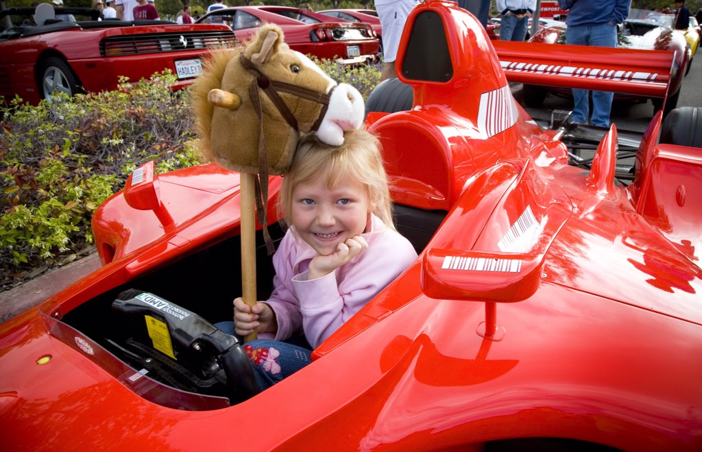 view of a Ferrari roadster racer at a car show in the morning and a young gril child sitting inside with a smile and a horse toy. : Stock Photo