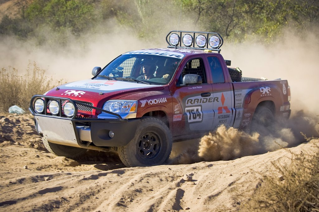 Baja Race Truck off road racer racing mud and dirt flying Offroad racing in the dirt desert : Stock Photo