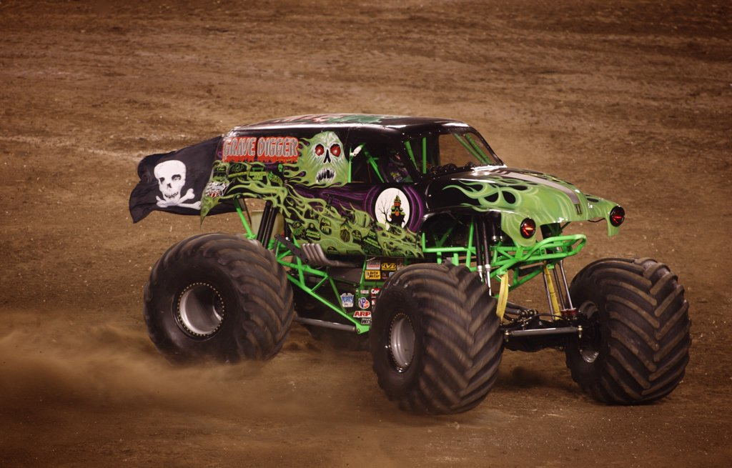 Grave digger Monster Truck at a Monster Truck Rally in Raymond James Stadium, Tampa, FL. A monster truck is an automobile, typically a pickup truck, which has been modified or purposely built with extremely large wheels and suspension. Typically, a monster truck show involves the truck crushing smaller vehicles beneath its huge tires. These trucks can run up and over most man-made barriers, so they are equipped with remote shut-off switches, called the Remote Ignition Interuptor (RII), to help p : Stock Photo