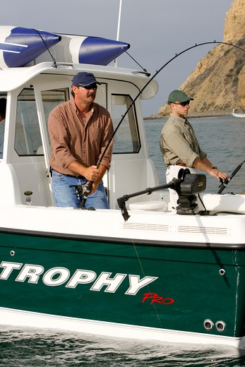 Guys / friends fishing in their Trophy 2359 Walkaround boat near the cliffs of San Diego, CA. Pacific Ocean. : Stock Photo
