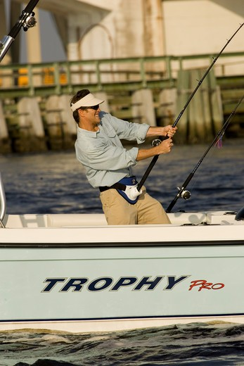 Guys / friends fishing near a bridge in San Carlos Bay, Fort Myers, Florida in a Trophy 2002 Walkaround boat. : Stock Photo