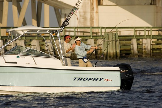 Stock Photo: 4093-7036 Guys / friends fishing near a bridge in San Carlos Bay, Fort Myers, Florida in a Trophy 2002 Walkaround boat.
