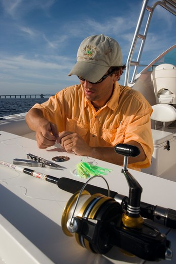 Stock Photo: 4093-7060 Fisherman rigging line with artificial lures on the rear / stern of a Trophy 2502 Walkaround boat.