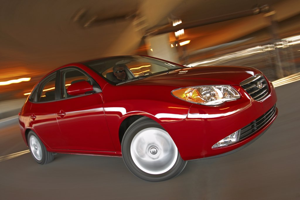 Front 3/4 action of a 2007 red Hyundai Elantra sedan. Inside a parking garage with lighting and turning. : Stock Photo