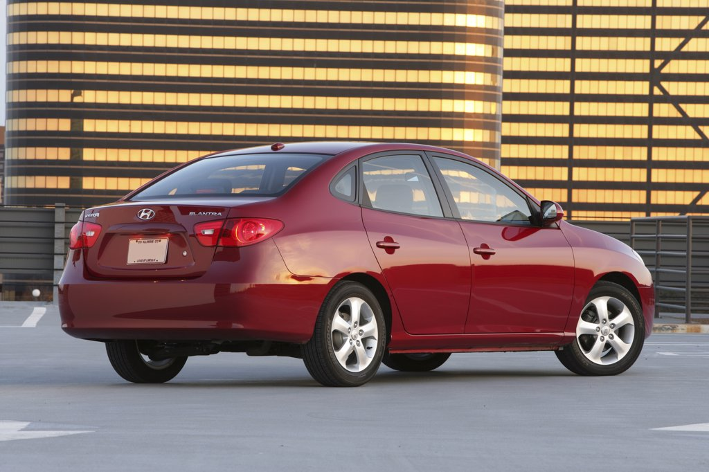 Rear 3/4 static view of a 2007 red Hyundai Elantra sedan. parked outside in front of a building reflective golden light : Stock Photo