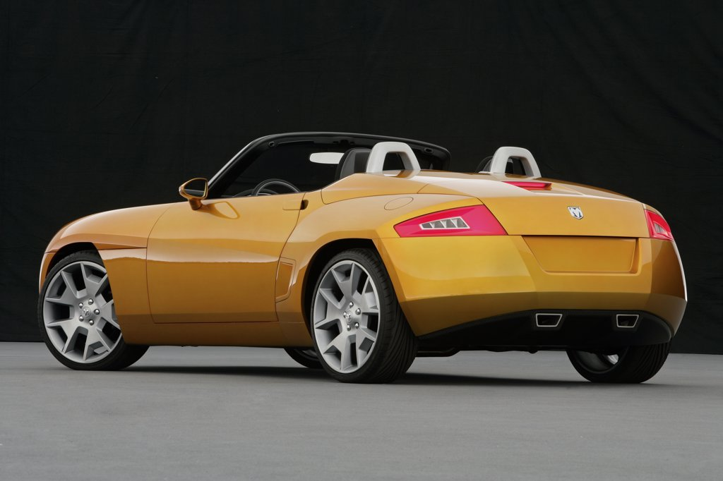Rear 3/4 view of a Dodge Demon Convertible concept. Gold color inside parked viewing with backdrop : Stock Photo