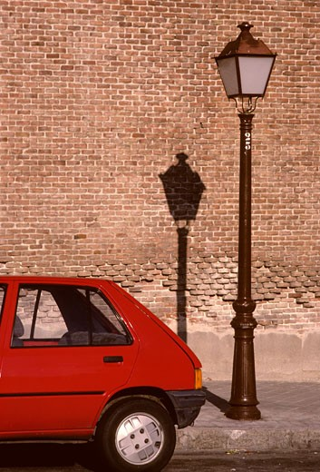hatchback red rear end street lamp light brick wall Madrid Spain city : Stock Photo