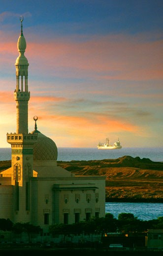 Stock Photo: 4093R-1815 A cargo ship leaving the Suez Canal with a mosque in the foreground. Egypt, Africa. Middle East