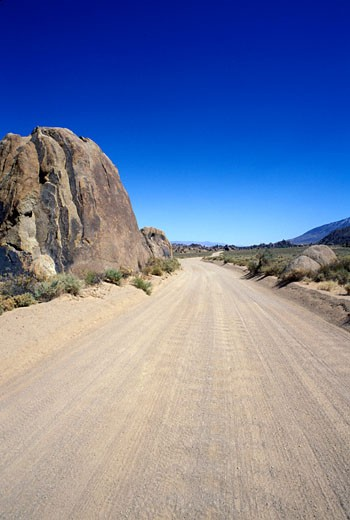 Stock Photo: 4093R-1871 Alabama Hills California sky rocks brush street