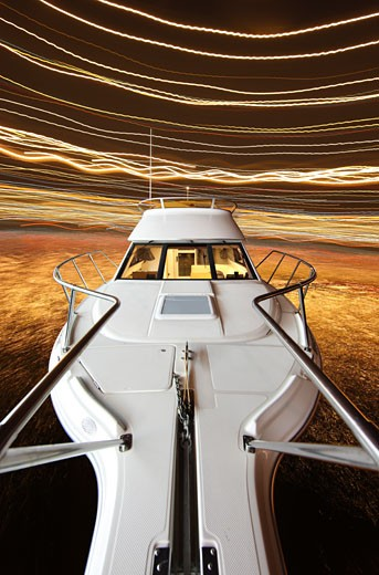 2005 Bayliner 288 cruising on lake at night, long exposure : Stock Photo