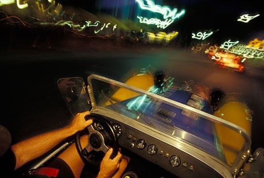 interior Lotus Super Seven 1970s yellow dashboard gauges hands steering wheel motion city lights street : Stock Photo