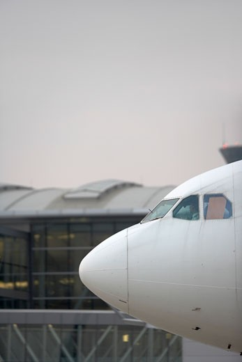 Stock Photo: 4093R-2106 Nose of airplane showing cockpit windows / windshield and airport in background Pearson International Airport, Toronto, ON, Canada