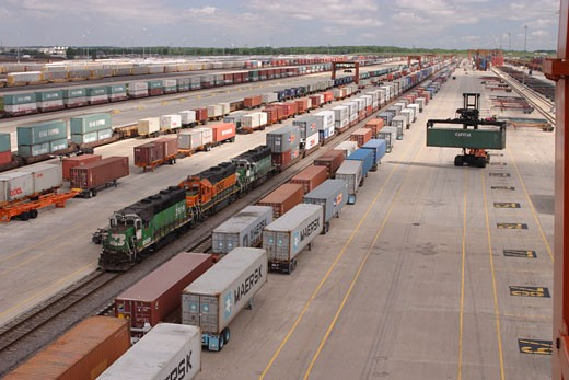 Cargo containers being loaded / unloaded from trucks to railroad cars at Logistics Park Chicago. BNSF Cargo container freight yard in Joliet,  Illinois. : Stock Photo