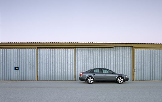 2002 Audi A4 1.8T parked near storage sheds airport hanger steel doors closed : Stock Photo