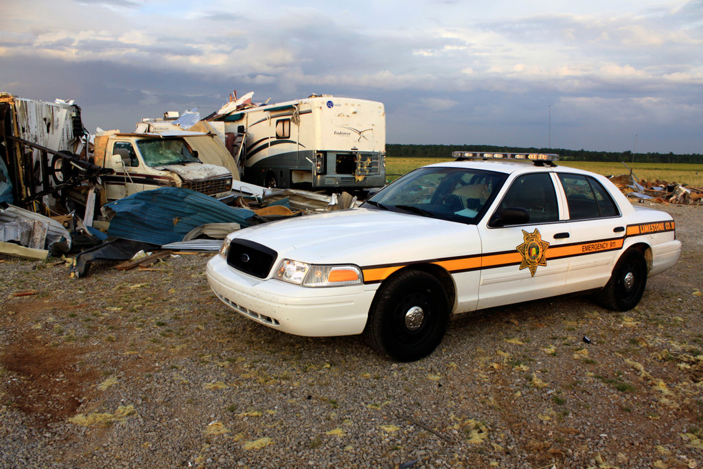 Sheriff deputy's vehicle sites near the wreckage of a storage building damaged by tornado, Tanner, Limestone County, Alabama, USA : Stock Photo