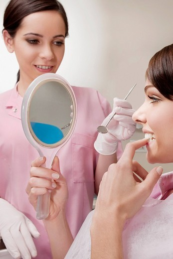 Stock Photo: 4105-1284 Woman looking into a mirror in dentist´s office