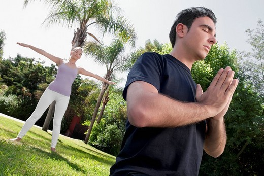 Stock Photo: 4105-1370 Couple practicing yoga in a park