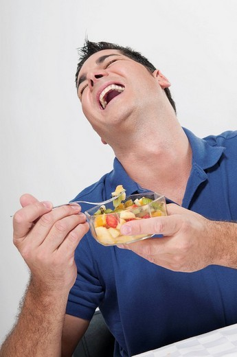 Man laughing while eating fruit salad : Stock Photo