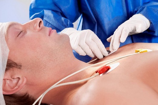 Stock Photo: 4105-1889 Surgeon attaching ECG electrodes on patient´s chest
