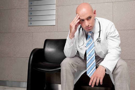 Doctor sitting on a chair and looking stressed : Stock Photo
