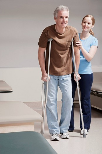 Physiotherapist assisting a patient in walking with crutches : Stock Photo