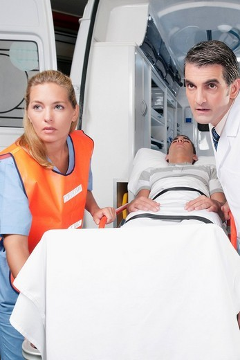 Paramedics leading a patient on a gurney from an ambulance : Stock Photo