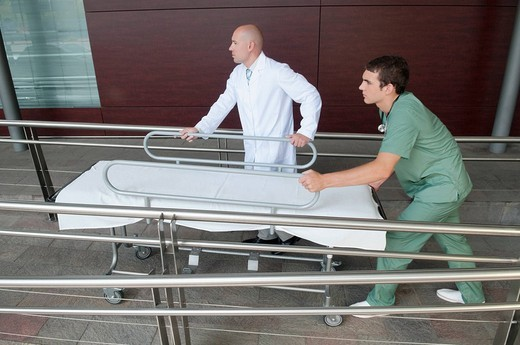 Doctor with a male nurse pushing a stretcher : Stock Photo