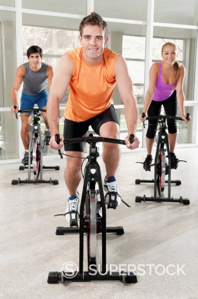 Stock Photo: 4105-2574 Three people working out on exercise bikes in a gym