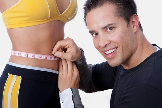 Man measuring the waist of a woman with a tape measure : Stock Photo
