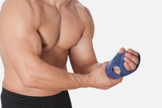 Mid section view of a man holding his wrist : Stock Photo