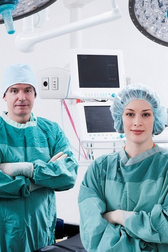 Surgeons smiling in an operating room : Stock Photo