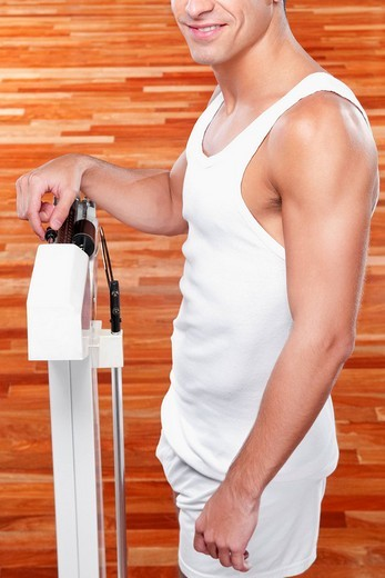 Man measuring his weight on a weighing scale : Stock Photo