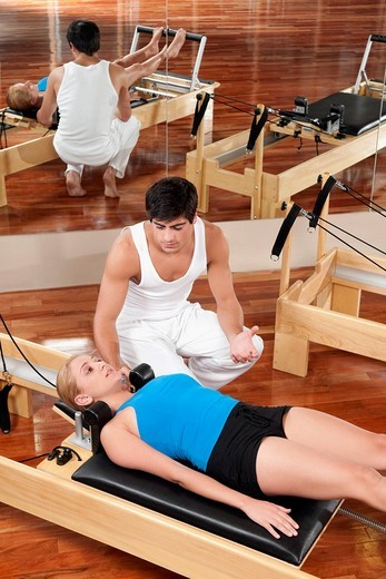 Stock Photo: 4105-3437 Male instructor assisting a woman in a gym