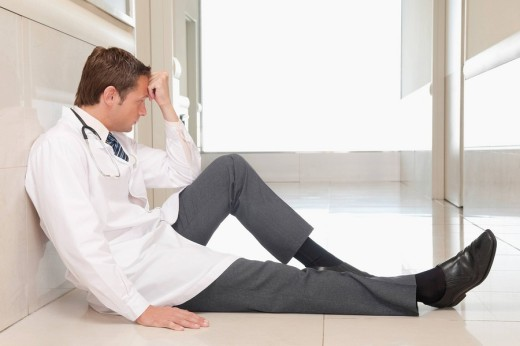 Doctor sitting on the floor looking depressed : Stock Photo