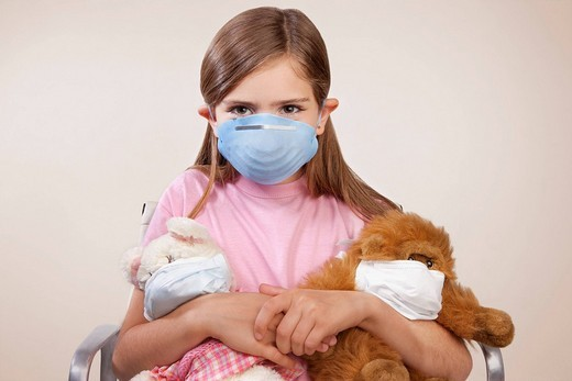 Stock Photo: 4105-3683 Portrait of a girl wearing a flu mask and holding stuffed toys