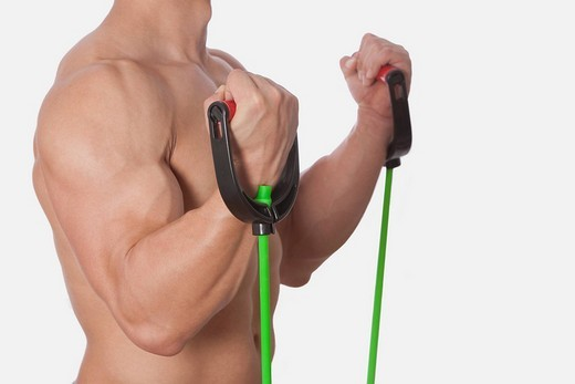 Mid section view of a man exercising with resistance band : Stock Photo