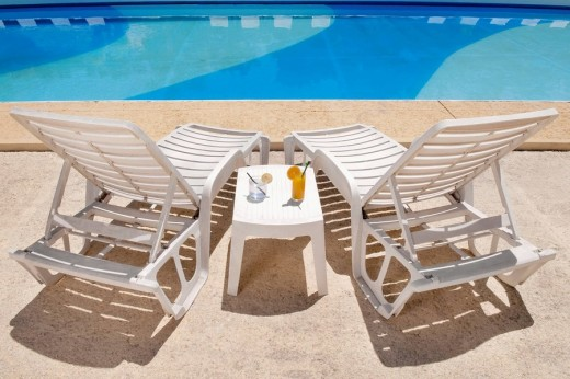 Stock Photo: 4105-3757 Lounge chairs with juices on table at the poolside