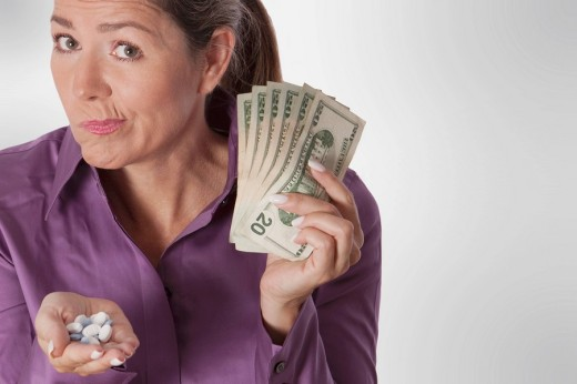 Woman holding pills and currency notes : Stock Photo