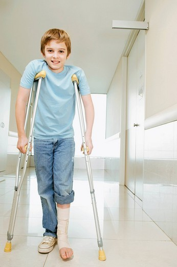 Stock Photo: 4105-3803 Boy standing with crutches and smiling