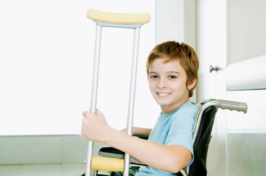 Stock Photo: 4105-3945 Boy holding crutch and sitting in a wheelchair