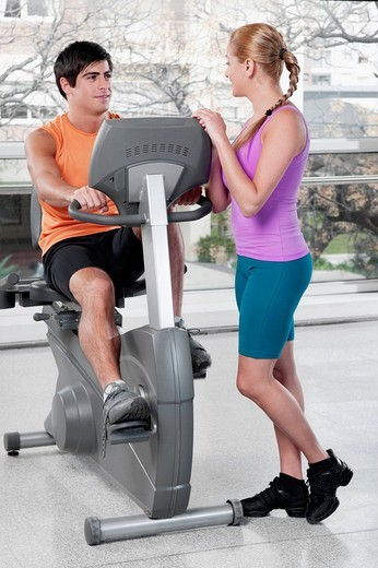 Stock Photo: 4105-4141 Woman talking to a man working out on an exercise machine in a gym
