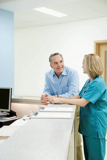 Stock Photo: 4105-4220 Female doctor talking with a patient at a reception counter in a hospital