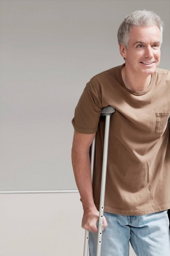 Patient walking with the help of crutches : Stock Photo