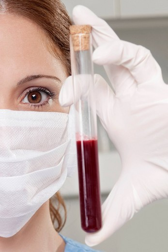 Female lab technician analyzing a blood sample in a test tube : Stock Photo